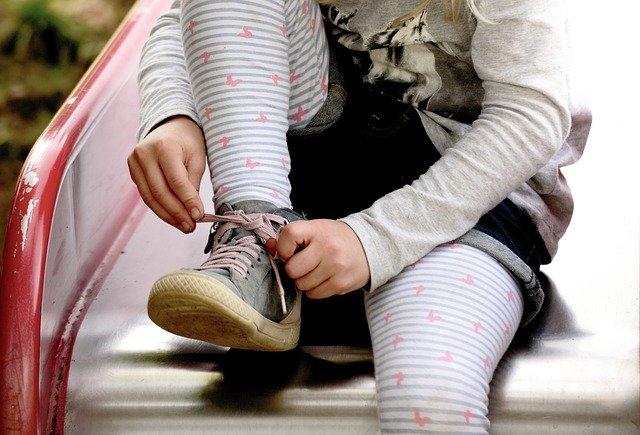 Dziewczynka wiąże swoje szare buciki