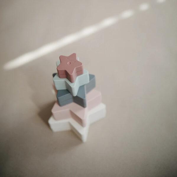 Zestaw 5 gwiazdek do składania i układania. Spadające gwiazdy oświetlają duńskie miasto Aarhus, aby dostać się do pokoju zabaw Twojego dziecka.Maluchy będą zachwycone dopasowywaniem stonowanych kolorów podczas odkrywania swoich zdolności motorycznych dzięki temu pięknemu zestawowi z gwiazdą gniazdowania. Zabawki do układania wieży i piramidy pomagają rozwijać zarówno motorykę dłoni, jak i mózg dzieci, począwszy od około 6-go m-ca życia. Podstawowe umiejętności zdobyte podczas układania stają się podstawą do bardziej złożonych zadań w przyszłości, takich jak rysowanie i pisanie. Zabawa piramidami do układania pomaga dzieciom w nauce języków. Układanka rekomendowana dla dzieci w wieku od 6 m-cy do 3 lat.