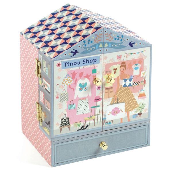 """Urocza szkatułka z pozytywką - pięknie zaprojektowane muzyczne pudełko na biżuterię w kształcie butiku Tinou. Szkatułka z trzema szufladami. Wewnątrz szkatułki znajduje się lusterko i figurka , która obraca się w takt grającej melodii. Pozytywka uruchamia się po otwarciu szkatułki i nakręceniu mechanizmu. Śliczna ozdoba do dziecięcego pokoju. Melodia pozytywki: Wolfganga Amadeusza Mozarta """"CZARODZIEJSKI FLET"""""""